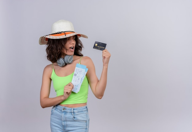 A surprised young woman with short hair in green crop top in headphones wearing sun hat holding plane tickets looking at credit card on a white background