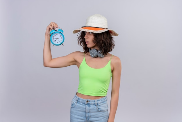 A surprised young woman with short hair in green crop top wearing sun hat looking at time holding blue alarm clock on a white background