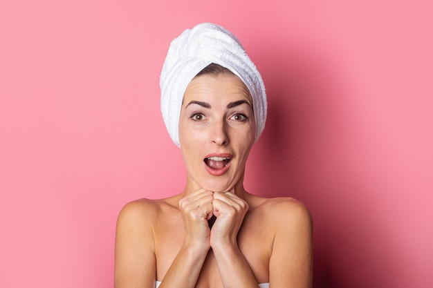 Surprised young woman with a towel on her head on pink background