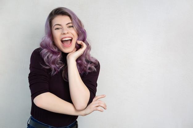 灰色の壁でポーズをとる波状の紫色の髪と自然な化粧で驚いた若い女性。テキスト用のスペース