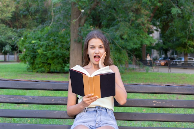 Surprised young woman with widely open yeas and mouth and a hand on cheek is reading a book outdoors.