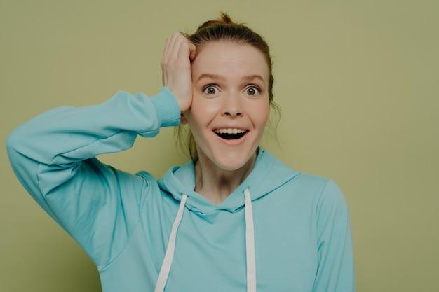 スタジオでポーズをとっている間カジュアルな青いフード付きセーターを着てカメラを見て頭に手を握ってショックと興奮を示す化粧なしで驚いた若い女性。人間の感情の概念