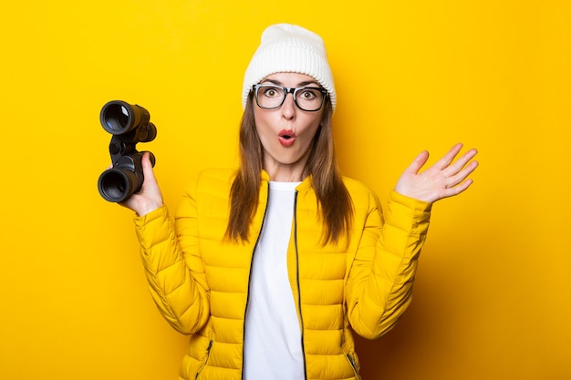 Surprised young woman in yellow jacket with binoculars on yellow surface