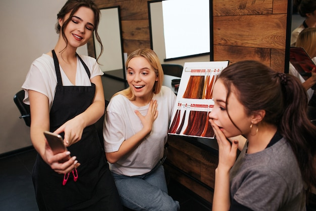 Surprised young women looking at phone while hairdresser holding it in hand