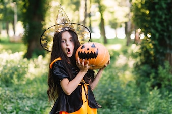 Surprising girl in witch costume holding pumpkin