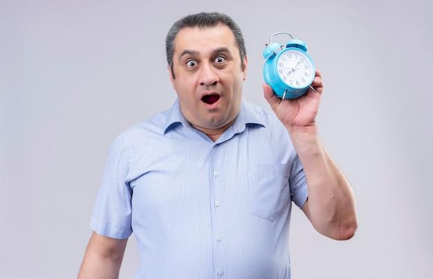 Удивительный мужчина средних лет в синей полосатой рубашке с синим будильником, стоя на белом фоне
