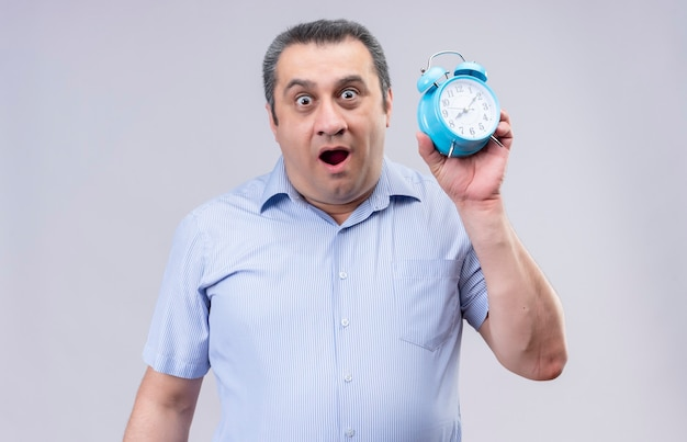 Surprising middle-aged man wearing blue vertical striped shirt holding blue alarm clock while standing on a white background