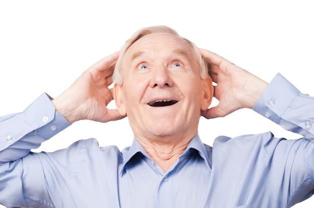 Удивительные новости. возбужденный старший мужчина держится за руки и смотрит в сторону, стоя на белом фоне