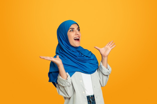 驚くべき。黄色で隔離の若いイスラム教徒の女性