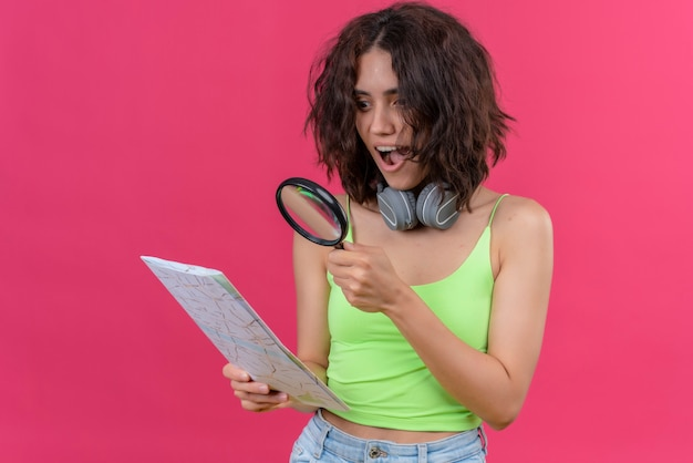 A surprising young pretty woman with short hair in green crop top in headphones looking at a map with magnifying glass