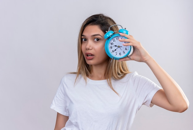 A surprising young woman in white t-shirt listening to clock ticking sound while holding blue alarm clock