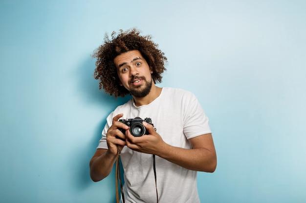 놀랍게도 곱슬 머리 brunet 남자가 사진을 찍고 찾고