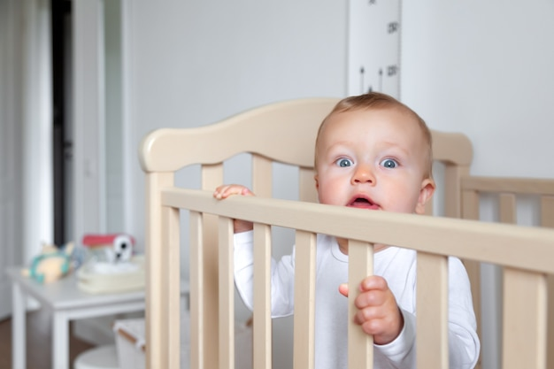 Surprized blond cute little blue-eyed baby in white bodysuit stands in wooden bed on background of interior of modern children's room, copy space, horizontal