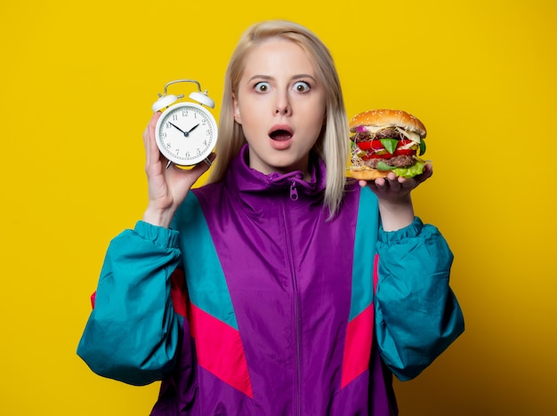 Surprsied girl in 80s clothes style with burger and alarm clock