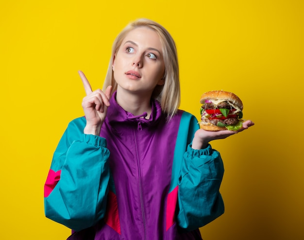 Surprsied girl in 80s clothes style with burger on yellow space