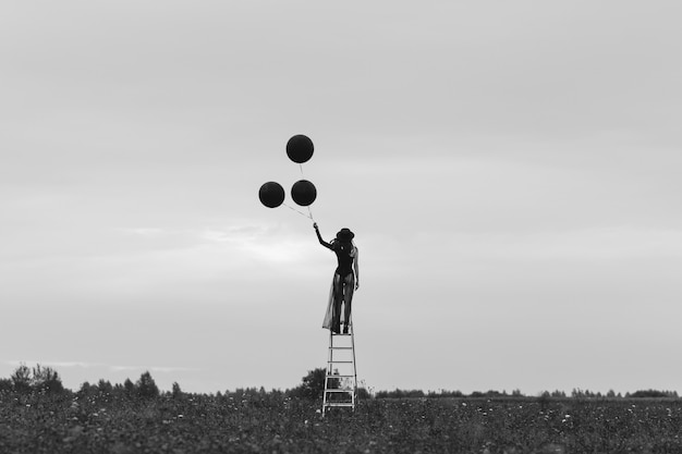 Surreal photo of a girl in a hat with balloons in her hand in a field