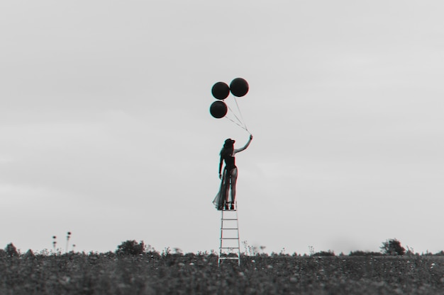 Surreal photo of a lonely girl on the stairs with balloons. the concept of freedom and independence. black and white with 3d glitch virtual reality effect