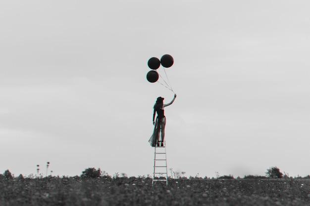 風船と階段の上の孤独な少女のシュールな写真。自由と独立の概念。 3dグリッチバーチャルリアリティ効果のある白黒