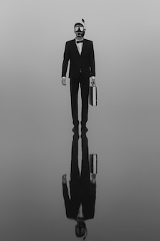 Surreal portrait of a man in a suit and mask with a diving tube with a briefcase in his hands standing on the water.