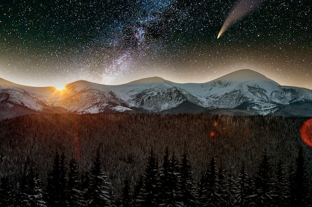 Surreal view of night in mountains with starry dark blue cloudy sky and c/2020 f3 (neowise) comet with light tail.
