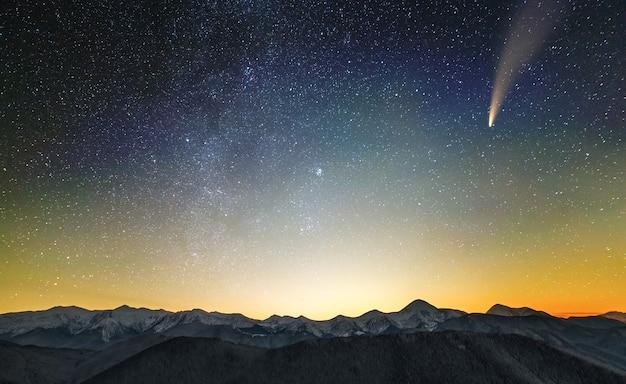 별이 빛나는 진한 파란색 흐린 하늘과 밝은 꼬리가있는 c / 2020 f3 (neowise) 혜성이있는 산에서 밤의 초현실적 인 전망.