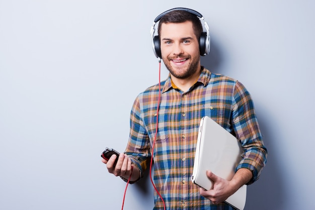 Surrounded by gadgets. handsome young man in headphones holding a laptop and smiling while standing against grey background