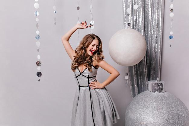 Окруженная огромными елочными шарами, молодая и чудесная женщина в праздничном наряде танцует и улыбается