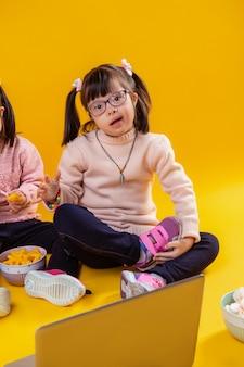 В окружении закусок. очаровательная темноволосая девушка с синдромом дауна сидит на полу со своей сестрой-близнецом
