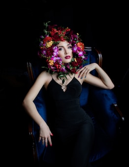 Surrounded face with colourful flowers, beautiful girl dressed in black dress on the blue armchair and bright make-up