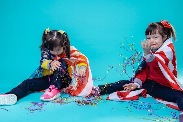 装飾に囲まれています。ホイルの装飾で遊んで、一緒にのんきな2人の面白い女の子