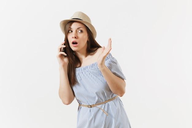 놀란 젊은 여성은 파란 드레스를 입고 모자에 몇 가지 문제가 있으며 흰색 배경에 격리된 휴대전화에서 가짜 뉴스나 예상치 못한 소문을 듣습니다. 사람, 진실한 감정, 라이프 스타일 개념.