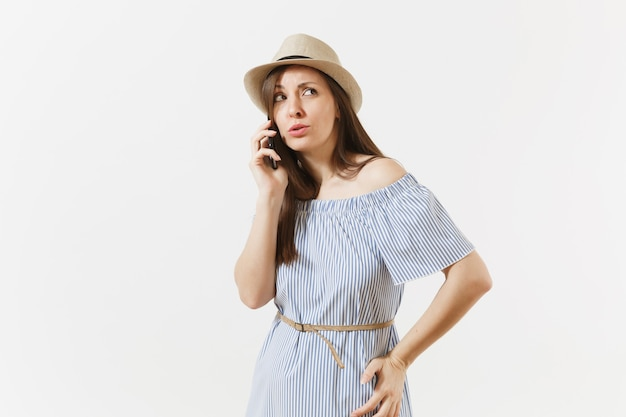 Surrprised upset young woman dressed blue dress, hat has some problems, hears fake news or unexpected rumor in mobile phone isolated on white background. people, sincere emotions, lifestyle concept.