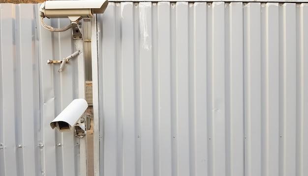 회색 골판지 금속 울타리 위에 있는 감시 카메라.