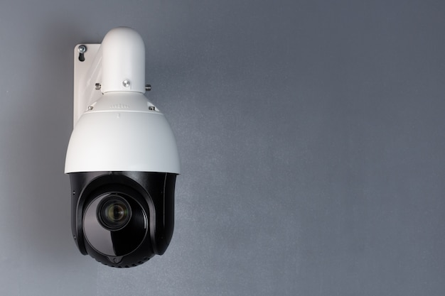 Surveillance cctv camera video security with space on blue background.
