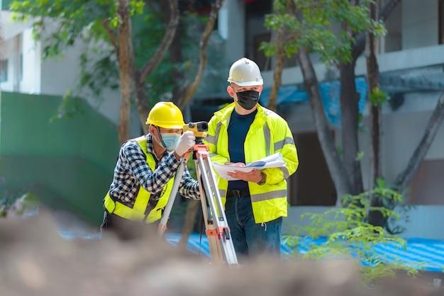 측량 팀 토목 기사는 건설 현장에서 측량 망원경을 사용하여 작업하고 있습니다. 건설 현장에서 건설 작업을 위한 측량 망원경의 사용. 측량에서 망원경을 사용하는 토목 기사.