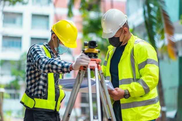Survey team civil engineer are working using survey telescope at the construction site. use of survey telescope for construction work at construction sites. civil engineer using telescope at survey.