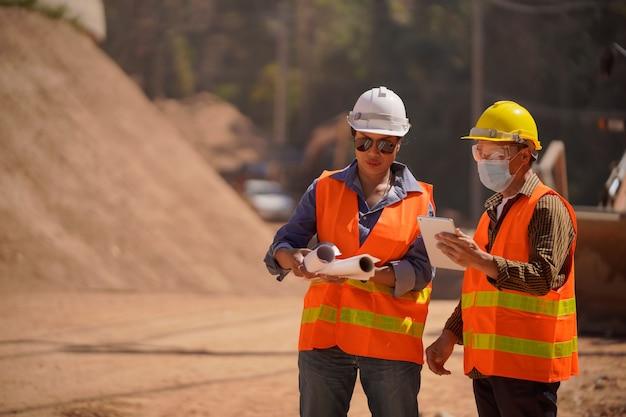 測量士ビルダーエンジニア道路男性と女性の技術者ビジネスチームは、道路建設現場のぼやけを通して建設現場の青写真を探しています。輸送開発のコンセプト。