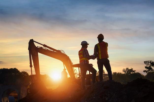道路工事でセオドライトを使用して測定を行う測量技師。建設現場の測量技師。