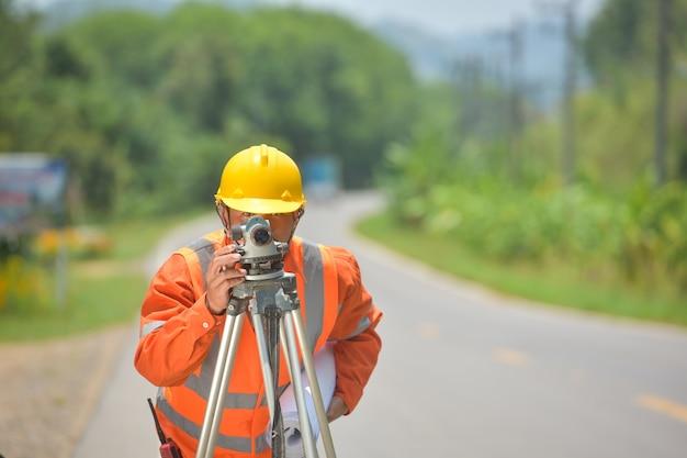 Инженер-геодезист, выполняющий измерения с теодолитом на дорожных работах. инженер-геодезист на строительной площадке.