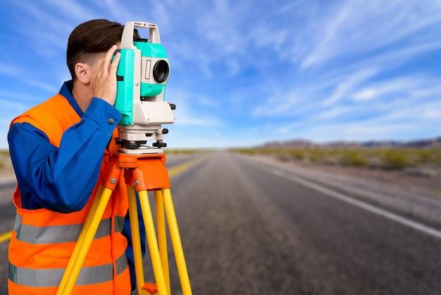 Инженер-геодезист на земле на фоне