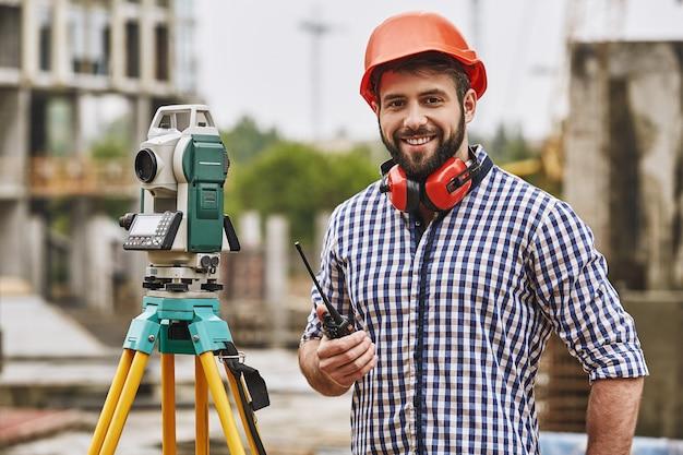 Инженер-инспектор геодезического оборудования в защитной одежде и красном шлеме с использованием геодезического оборудования