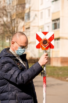 Surveyor holds a geodetic pole in a protective mask