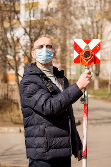 Surveyor holds a pole in a protective mask