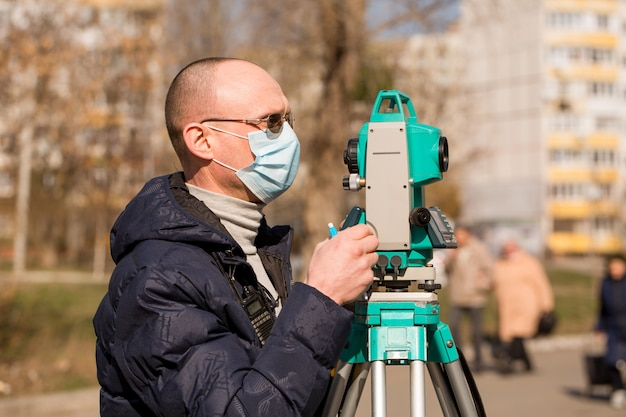 Surveyor in a protective mask works