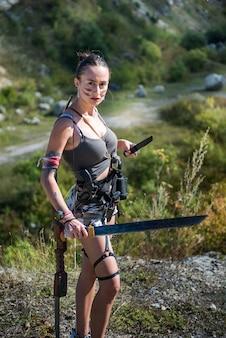Survivor woman with machete in short summer cloth in nature, lifestyle