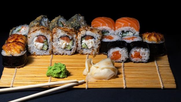 Суши набор суши-роллов на бамбуковой сервировке с имбирем васаби и палочками для еды.