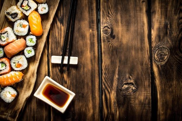 Суши и роллы из морепродуктов с соевым соусом. на деревянном фоне.