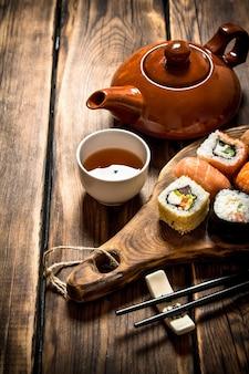 Суши и роллы с травяным чаем. на деревянном столе.