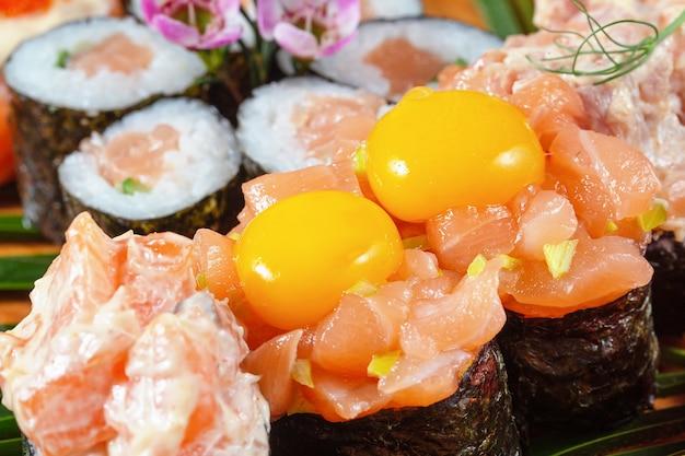 赤い魚と生のウズラの卵を添えた寿司とロール。断片