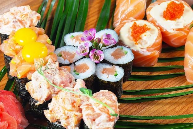 緑の葉と木の板にソースと生のウズラの卵と寿司とロール